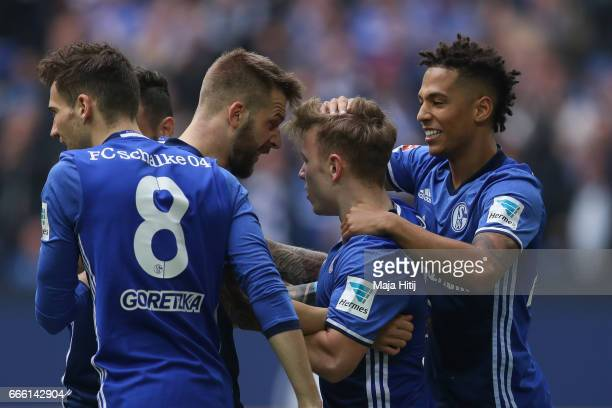 Guido Burgstaller of Schalke celebrates with his team-mates after scoring a goal to make it 1-0 during the Bundesliga match between FC Schalke 04 and...