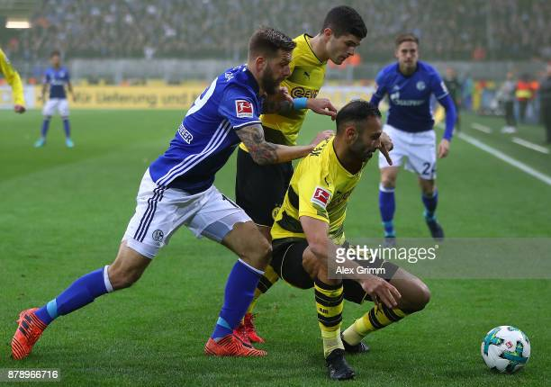 Guido Burgstaller of Schalke fights for the ball with Christian Pulisic of Dortmund and Oemer Toprak of Dortmund during the Bundesliga match between...
