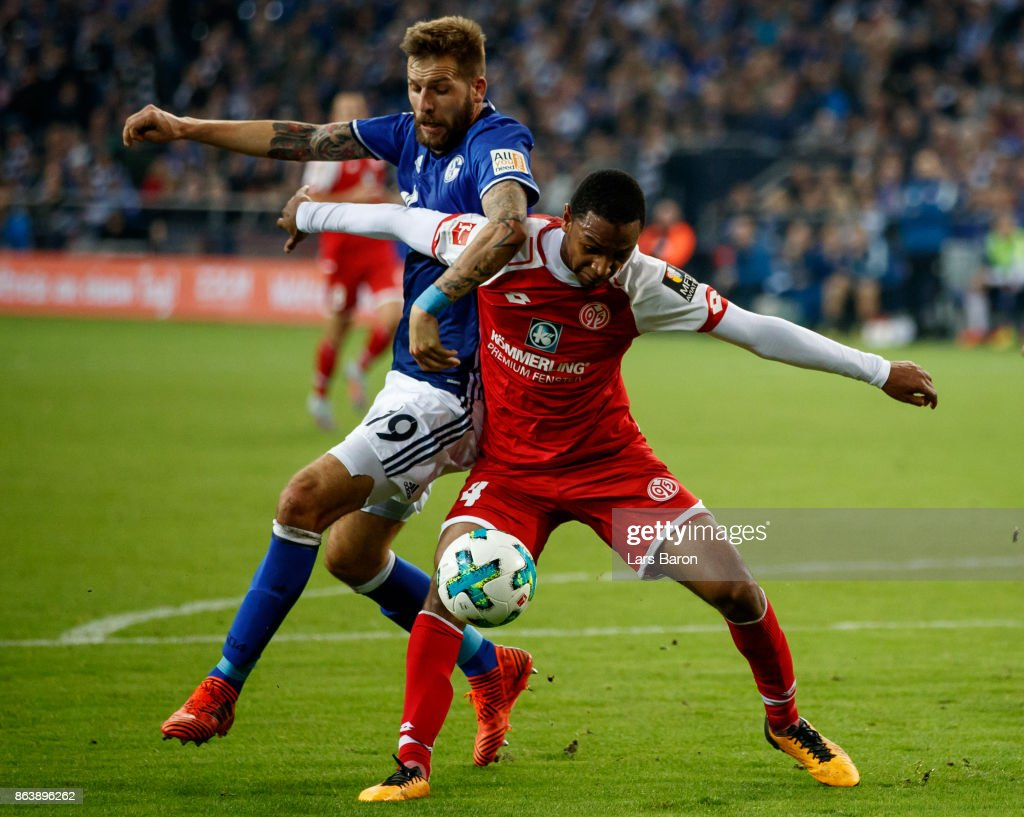Guido Burgstaller of Schalke is challenged by Abode Diallo of Mainz during the Bundesliga match between FC Schalke 04 and 1. FSV Mainz 05 at Veltins-Arena on October 20, 2017 in Gelsenkirchen, Germany.