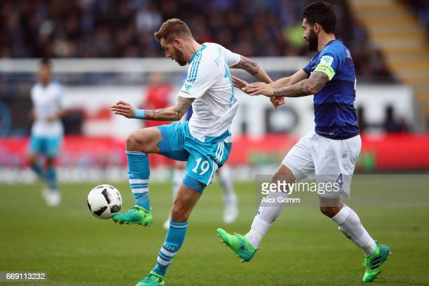 Guido Burgstaller of Schalke is challenged by Aytac Sulu of Darmstadt during the Bundesliga match between SV Darmstadt 98 and FC Schalke 04 at...