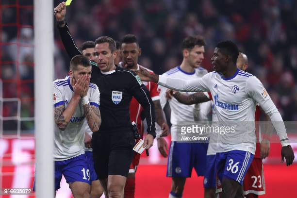Guido Burgstaller of Schalke is shown a yellow card by referee Tobias Stieler after diving in the penalty area during the Bundesliga match between FC...