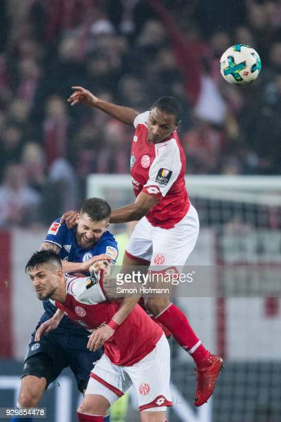 Guido Burgstaller of Schalke jumps for a header with Danny Latza and Abdou Diallo of Mainz during the Bundesliga match between 1 FSV Mainz 05 and FC...