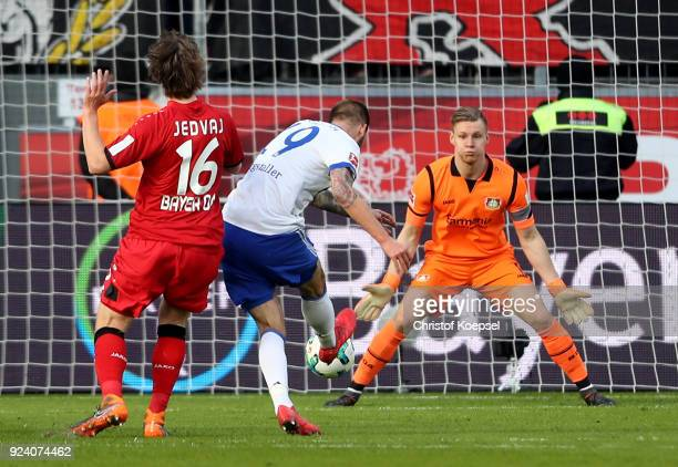Guido Burgstaller of Schalke scores the first goal against Tin Jedvaj and Bernd Leno of Leverkusen during the Bundesliga match between Bayer 04...