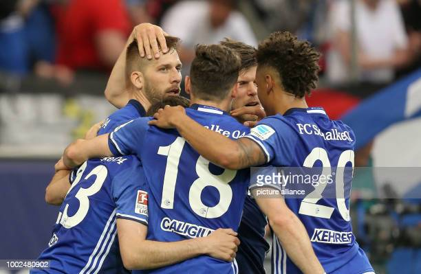 Guido Burgstaller of Schalke who scored and his teammates Daniel Caligiuri KlaasJan Huntelaar and Thilo Kehrer cheer during the German Bundesliga...