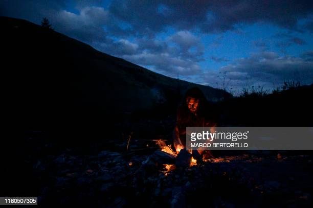 TOPSHOT Guido Camia dressed as a Neanderthal Cave man lights a campfire in Chianale in the Italian Alps near the French border on August 7 2019 Camia...
