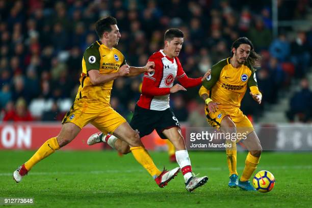 Guido Carrillo of Southampton is challenged by Lewis Dunk of Brighton and Hove Albion and Matias Ezequiel Schelotto of Brighton and Hove Albion...