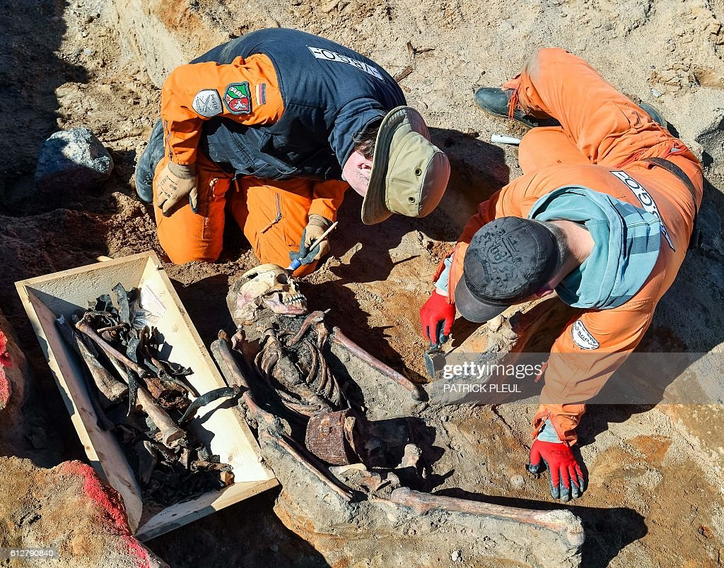 Guido Lewandowski (L) and Daniel Herrmann of the Association for the Recovery of the Fallen in Eastern Europe (VBGO) uncover the skeleton of a German soldier who died during Word War II on October 4, 2016 in Klessin, northeastern Germany. More than 70 years after the end of the Second World War, members of the association still are 'searching for the nameless dead, who lie in the mass graves of war without commemorative stones or who were buried somewhere and are still considered missing'. / AFP / dpa / Patrick Pleul / Germany OUT