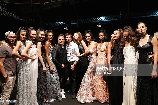 Guido Maria Kretschmer and Andre Maertens pose with models backstage after the Guido Maria Kretschmer show during the MercedesBenz Fashion Week...