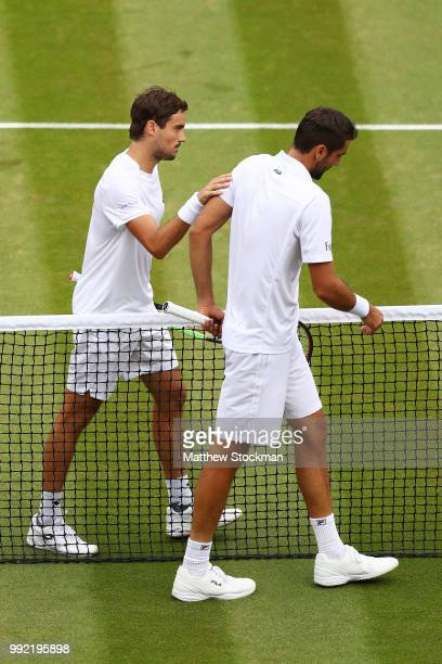 Guido Pella of Argentina consoles Marin Cilic of Croatia after their Men's Singles second round match on day four of the Wimbledon Lawn Tennis...