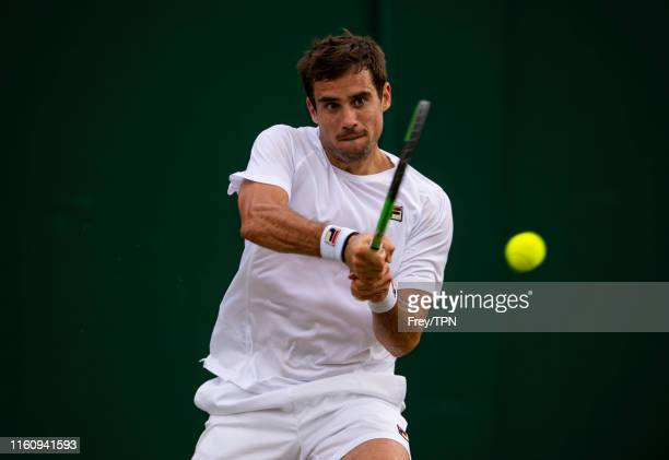 Guido Pella of Argentina hits a backhand against Milos Raonic of Canada during Day 7 of The Championships Wimbledon 2019 at All England Lawn Tennis...