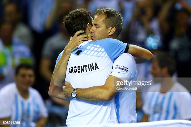 Guido Pella of Argentina is congratulated by Argentina team captain Daniel Orsanic following his victory in his singles match against Kyle Edmund of...