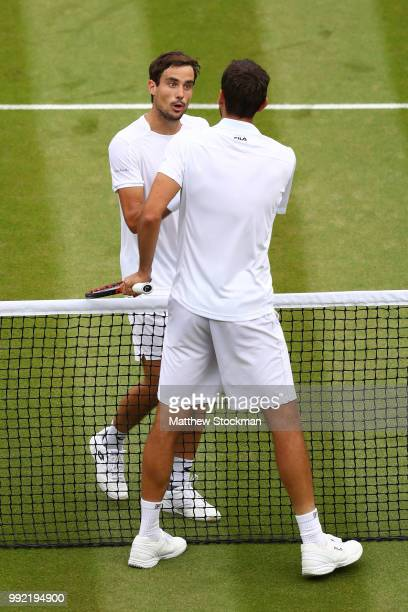 Guido Pella of Argentina shakes hands with Marin Cilic of Croatia after their Men's Singles second round match on day four of the Wimbledon Lawn...