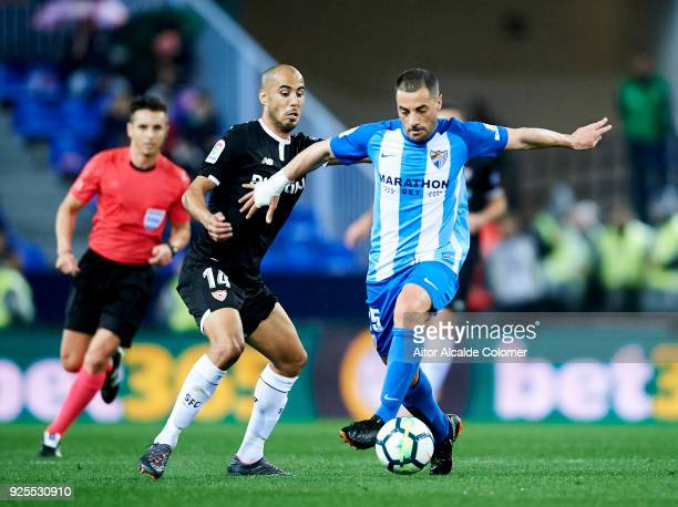 Guido Pizarro of Sevilla FC duels for the ball with Medhi Lacen of Malaga CF during the La Liga match between Malaga CF and Sevilla FC at Estadio La...