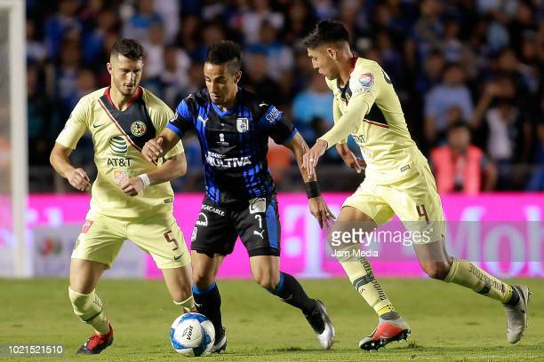 Guido Rodriguez of America Camilo Sanvezzo of Queretaro and Edson Alvarez of America competes for the ball during the fifth round match between...