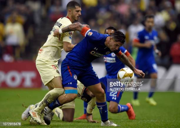 Guido Rodriguez of America vies for the ball with Milton Caraglio of Cruz Azul during the first round of final of the Mexican Apertura tournament...