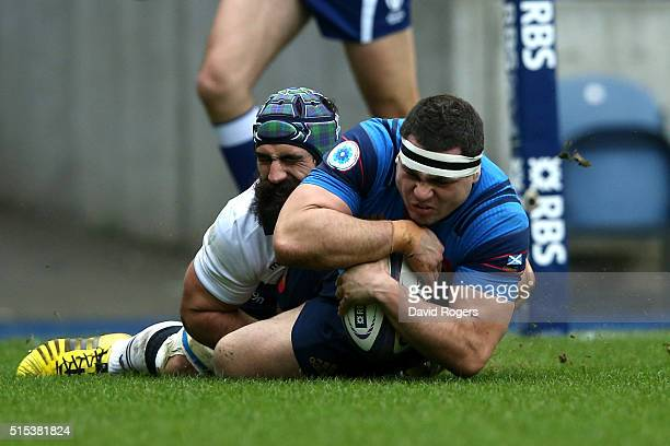 Guilhem Guirado of France scores the opening try despite the tackled from Josh Strauss of Scotland during the RBS Six Nations match between Scotland...