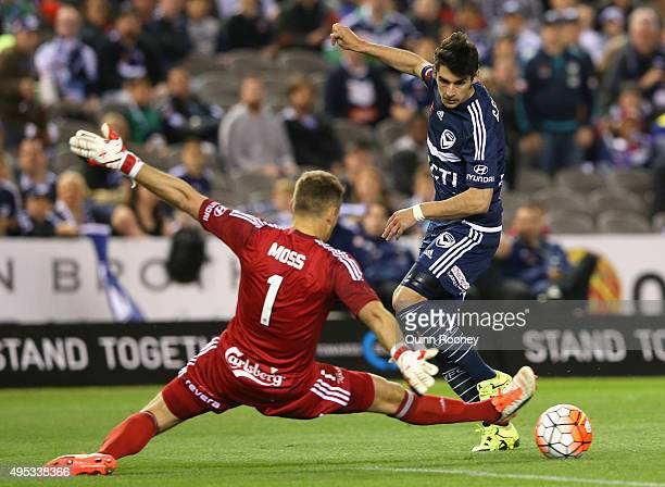 Guilherme Finkler of the Victory kicks the ball past Glen Moss of Phoenix during the round four ALeague match between the Melbourne Victory and...