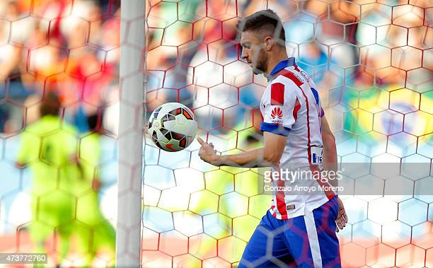 Guilherme Siqueira of Atletico Madrid picks the balll out of the net as Lionel Messi of Barcelona scores the first goal during the La Liga match...