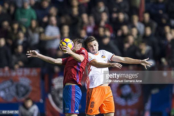 Guilherme Siqueira of Valencia CF duels for the ball with Oriol Riera of CA Osasuna during the La Liga match between CA Osasuna and Valencia CF at...