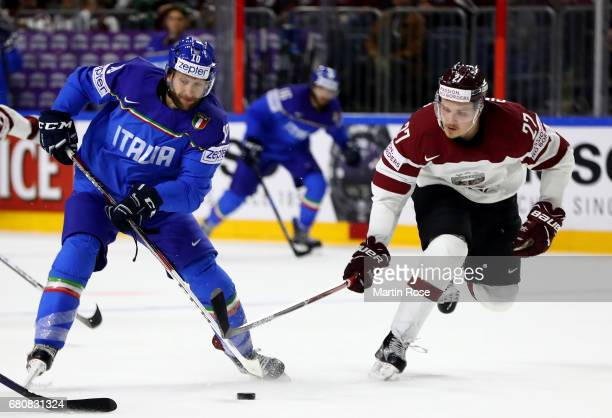Guilio Scandella of Italy challenges Oskars Cibulskis of Latvia for the puck during the 2017 IIHF Ice Hockey World Championship game between Italy...