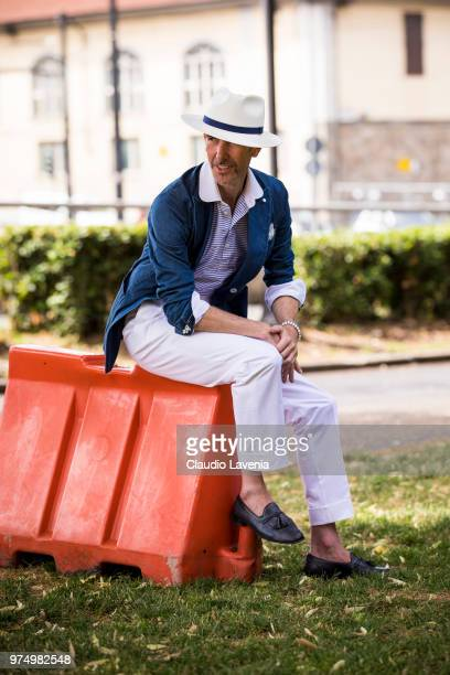 Guillaume Bo wearing a denim blazer striped shirt and white trousers is seen during the 94th Pitti Immagine Uomo at Fortezza Da Basso on June 14 2018...