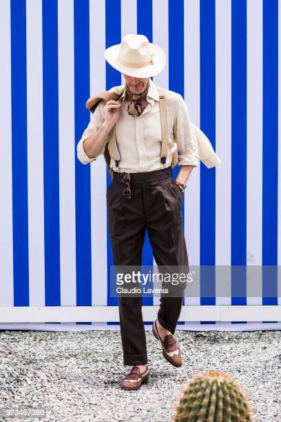 Guillaume Bo wearing headscarf white hat white blazer and shirt brown trousers and brown loafers is seen during the 94th Pitti Immagine Uomo at...