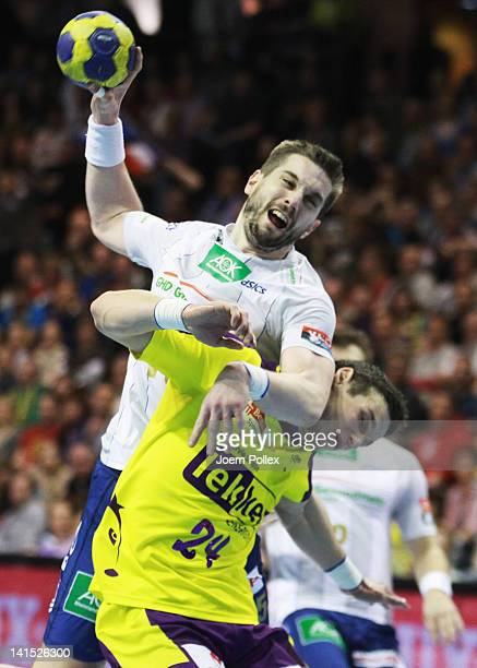 Guillaume Gille of Hamburg is challenged by Bartlomiej Jaszka of Berlin during the EHF Champions League round of sixteen match between Fuechse Berlin...