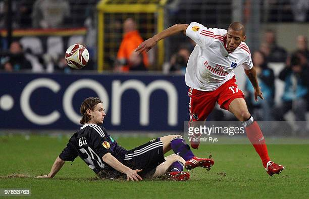 Guillaume Gillet of Anderlecht slides into Jerome Boateng of Hamburg during the UEFA Europa League round of 16 second leg match between RSC...