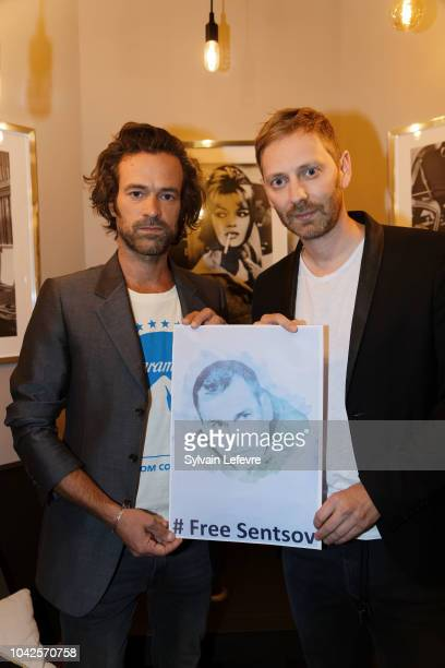 Guillaume Senez and Romain Duris hold a photo of the Ukrainian filmmaker Oleg Gennadyevich Sentsov to support the international campaign for the...