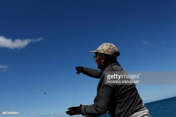 Guillermina Rivera throws out a fishing line in Vieques Puerto Rico on November 26 2017 / AFP PHOTO / Ricardo ARDUENGO / TO GO WITH AFP STORY BY...