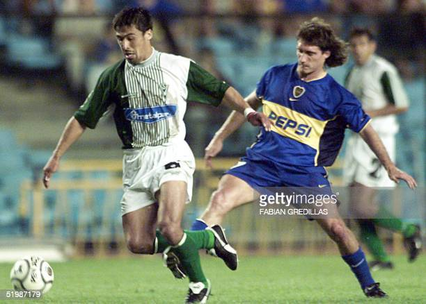 Guillermo Barros Schelotto of the Boca Juniors fights for the ball against Victor Cancino of Santiago's Wanderers 13 February 2002 in the 'La...