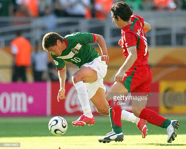 Guillermo Franco of Mexico puts his head down and speeds away from Andranik Teymourian of Iran in soldout Franken stadium Nuremberg Germany on June...