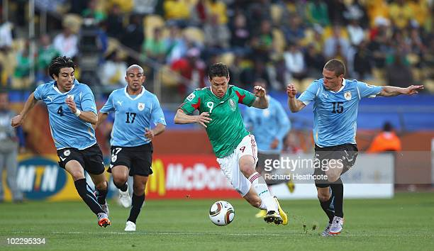 Guillermo Franco of Mexico runs with the ball as he is closed down by Jorge Fucile Egidio Arevalo and Diego Perez of Uruguay during the 2010 FIFA...