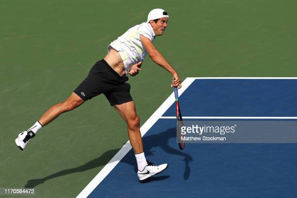 Guillermo Garcia-Lopez of Spain serves against John Isner of the United States during their Men's Singles first round match on day two of the 2019 US...