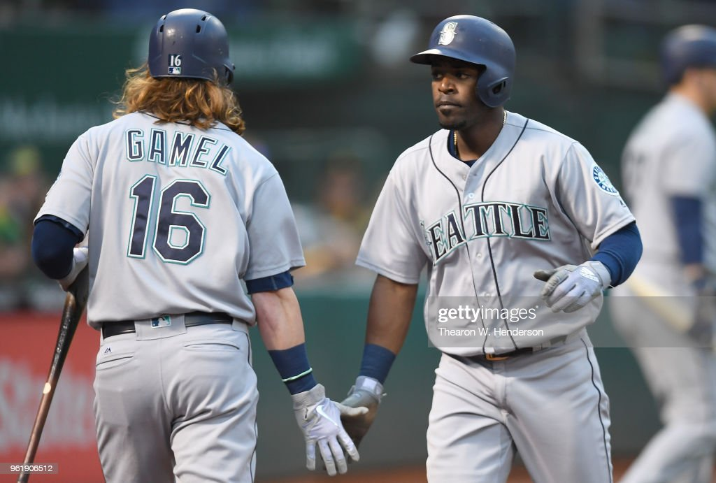 Guillermo Heredia #5 of the Seattle Mariners is congratulated by Ben Gamel #16 after Heredia scored against the Oakland Athletics in the top of the fourth inning at the Oakland Alameda Coliseum on May 23, 2018 in Oakland, California.