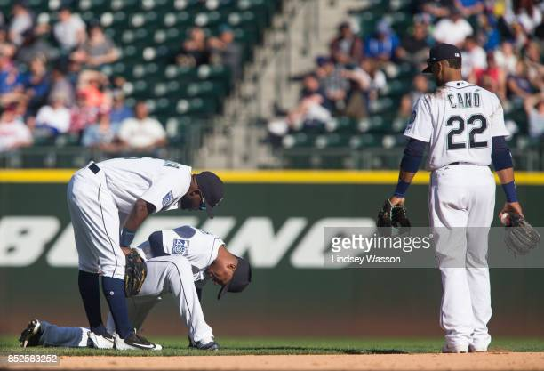 Guillermo Heredia of the Seattle Mariners left and Robinson Cano come to check on Jean Segura after Segura was hit in the hand by a throw from...