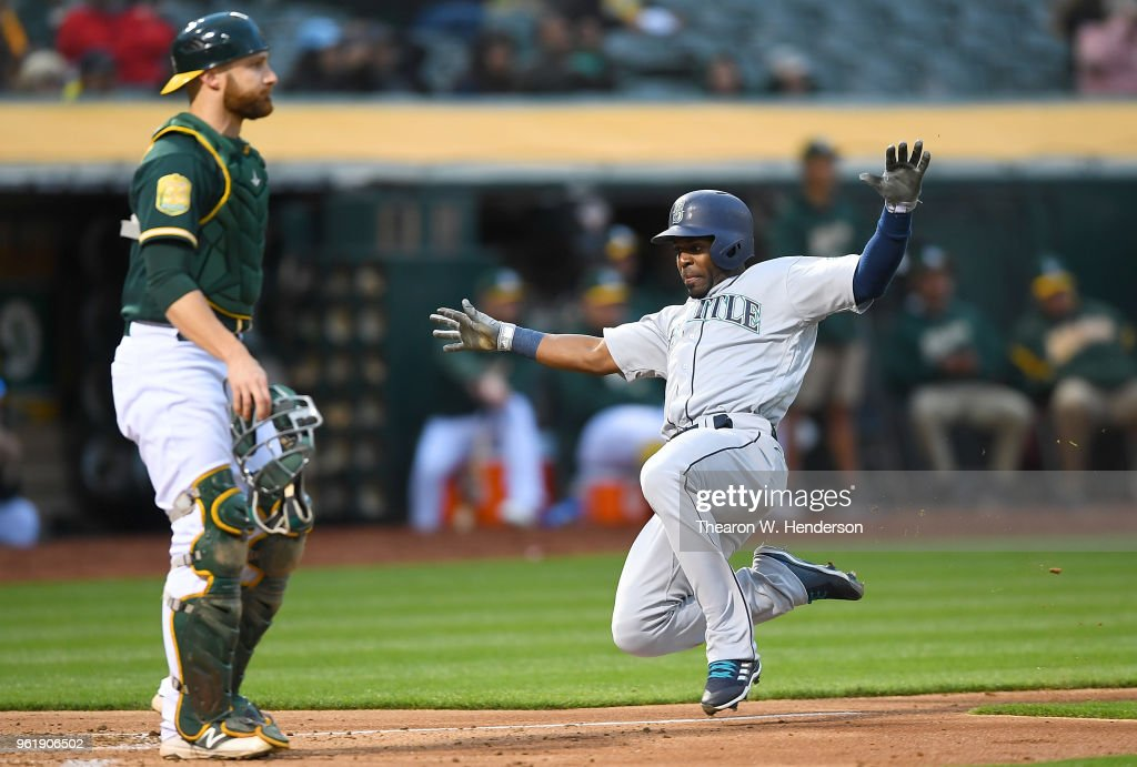 Guillermo Heredia #5 of the Seattle Mariners scores sliding past Jonathan Lucroy #21 of the Oakland Athletics in the top of the fourth inning at the Oakland Alameda Coliseum on May 23, 2018 in Oakland, California.