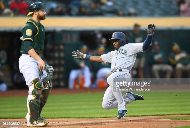 Guillermo Heredia of the Seattle Mariners scores sliding past Jonathan Lucroy of the Oakland Athletics in the top of the fourth inning at the Oakland...