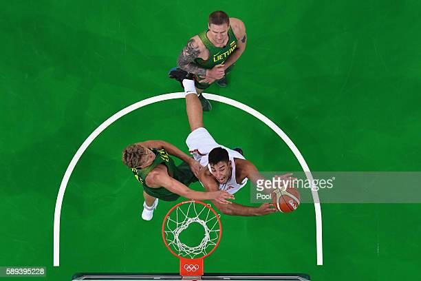 Guillermo Hernangomez Geuer of Spain goes to the basket against Antanas Kavaliauskas and Robertas Javtokas of Lithuania on Day 8 of the Rio 2016...