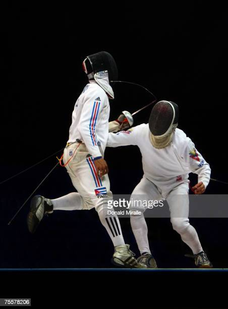 Guillermo Madrigal of Cuba breaks his sword on Wolfgang Mejias of Venezula in the Gold Medal Final of the Men's Team Sabre during the XV Pan American...