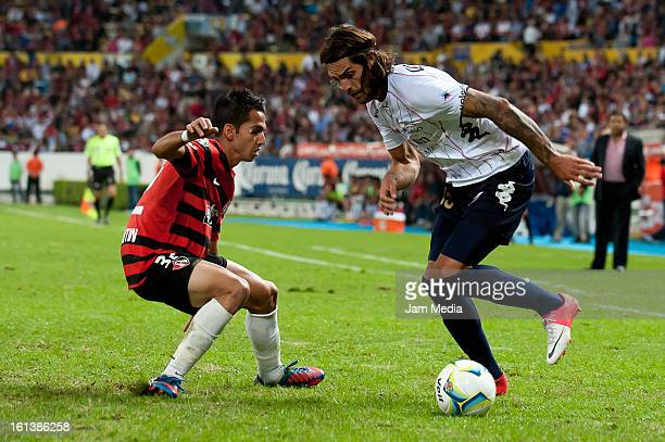Guillermo Martin of Atlas struggles for the ball with Joaquin Larrivery of Atlante during the match as part of the Clausura 2013 Liga MX at Estadio...