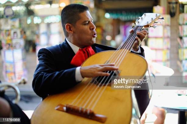 Guillermo Nunez a member of the allfemale strolling Mariachi band Ellas Son plays the guithrron as he performs at Los Angeles Farmer Market during...