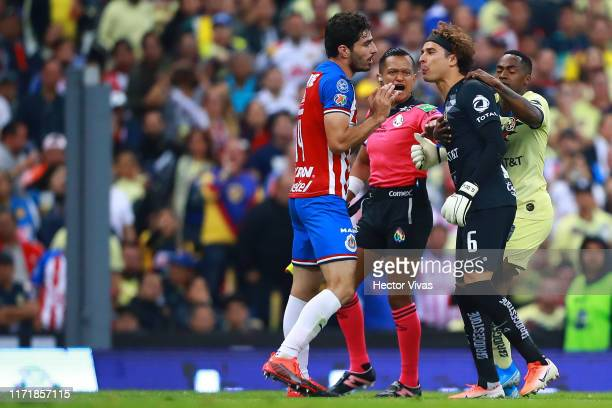 Guillermo Ochoa of America spits to Antonio Briseno of Chivas after a foul against Giovani Dos Santos of America during the 12th round match between...
