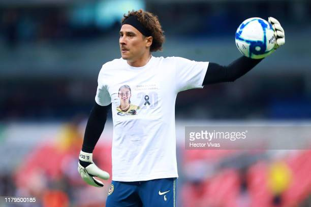 Guillermo Ochoa of America wears a shirt with a portrait of the player Diana Gonzalez of the women's America team who died yesterday at the age of 26...