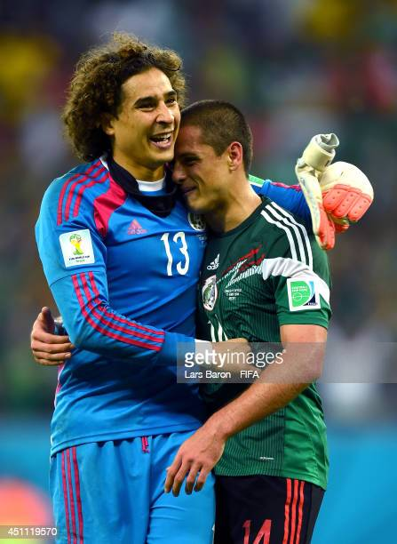 Guillermo Ochoa of Mexico celebrates with Javier Hernandez of Mexico after winning the 2014 FIFA World Cup Brazil Group A match between Croatia and...