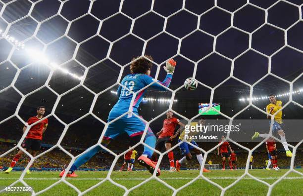 Guillermo Ochoa of Mexico makes a save after a header by Thiago Silva of Brazil during the 2014 FIFA World Cup Brazil Group A match between Brazil...