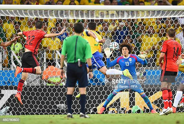 Guillermo Ochoa of Mexico tries to stop a header by Thiago Silva of Brazil during the 2014 FIFA World Cup Brazil Group A match between Brazil and...