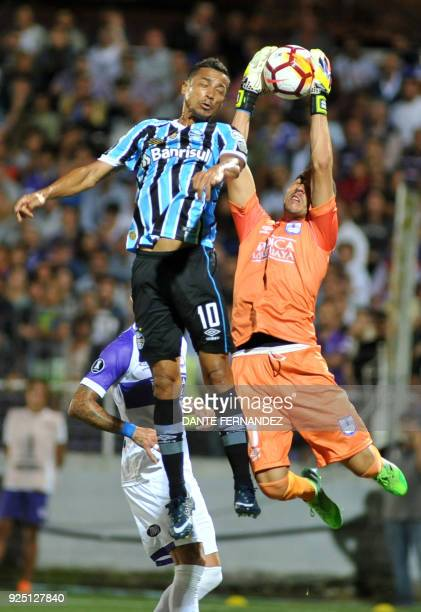 Guillermo Reyes of Uruguayan Defensor Sporting catches the ball next to Cicero of Brazilian Gremio during a 2018 Copa Libertadores football match at...
