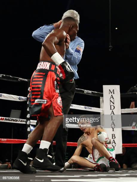 Guillermo Rigondeaux is held by referee Vik Drakulich after knocking down Moises Flores during their super bantamweight championship bout at the...