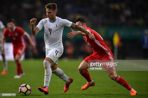 Guillermo Varela left of Uruguay national football team kicks the ball to make a pass against Connor Roberts of Wales national football team in their...